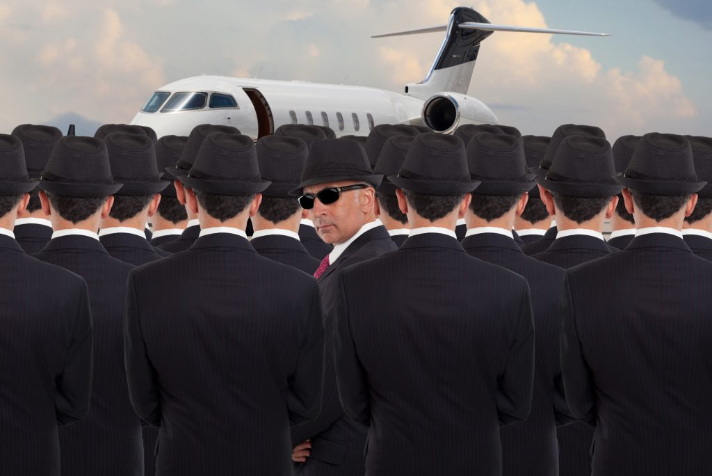 Several business men standing by a jet with one person looking at the camera
